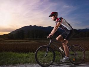 young-man-training-on-mountain-bike-at-sunset